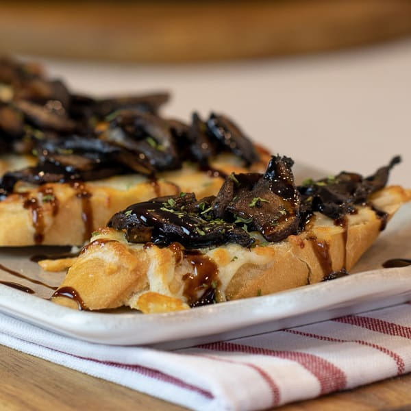 This unique bruschetta has toasted baguettes with melted mozzarella and parmesan. Topped with sautéed portobello mushrooms and drizzled with balsamic glaze.