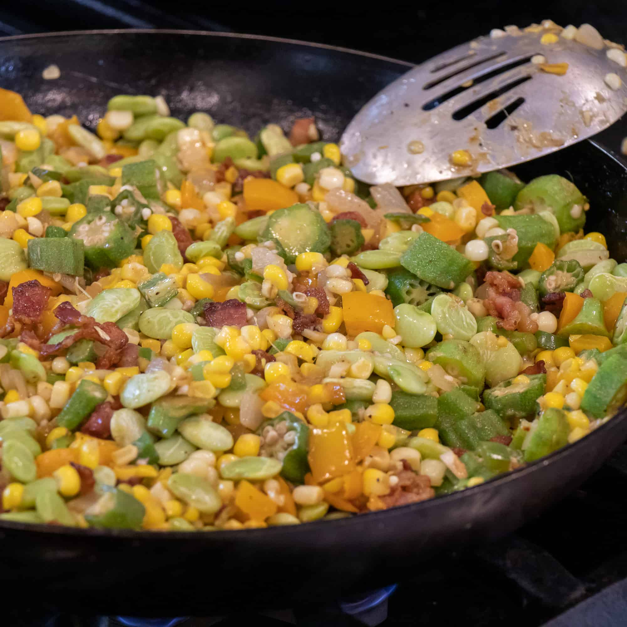 Easy skillet recipe for how to make succotash with lima beans, bacon, corn, okra, grape tomatoes. Classic southern side dish comfort food.