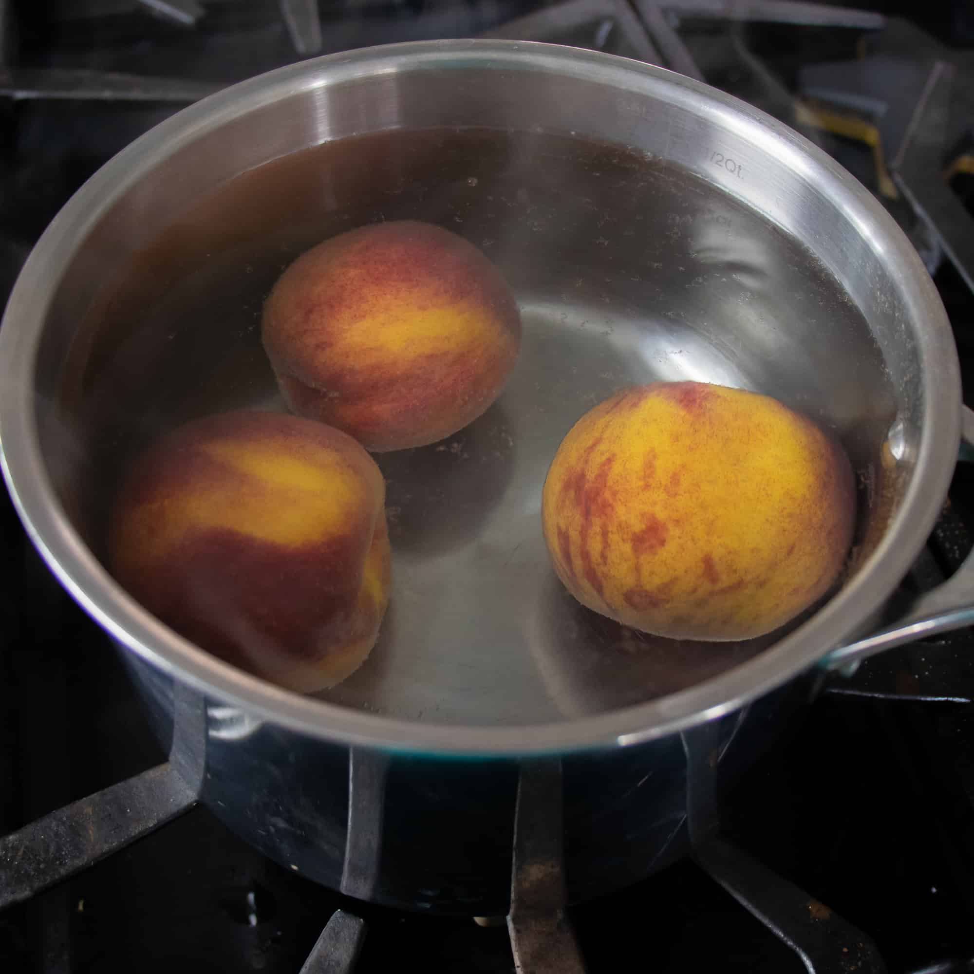 Drop the peaches in hot water to blanch for one minute