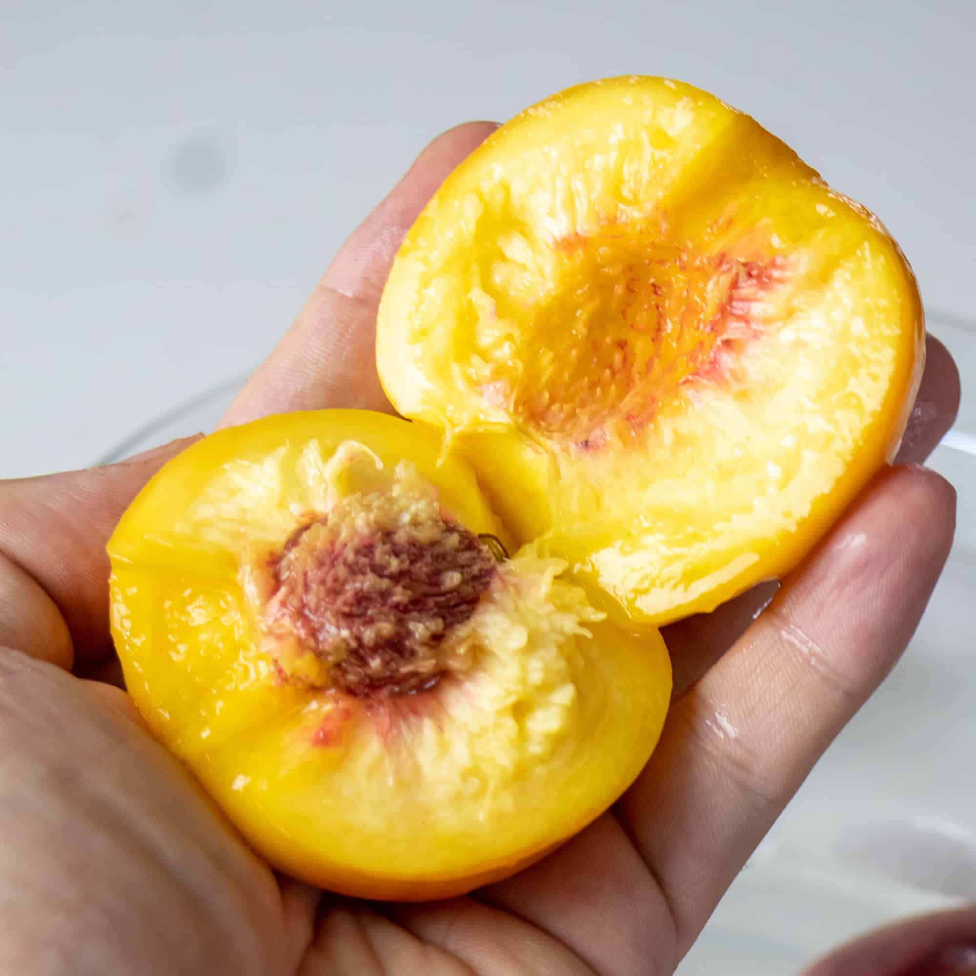 Cut the peach in half around the pit and remove.