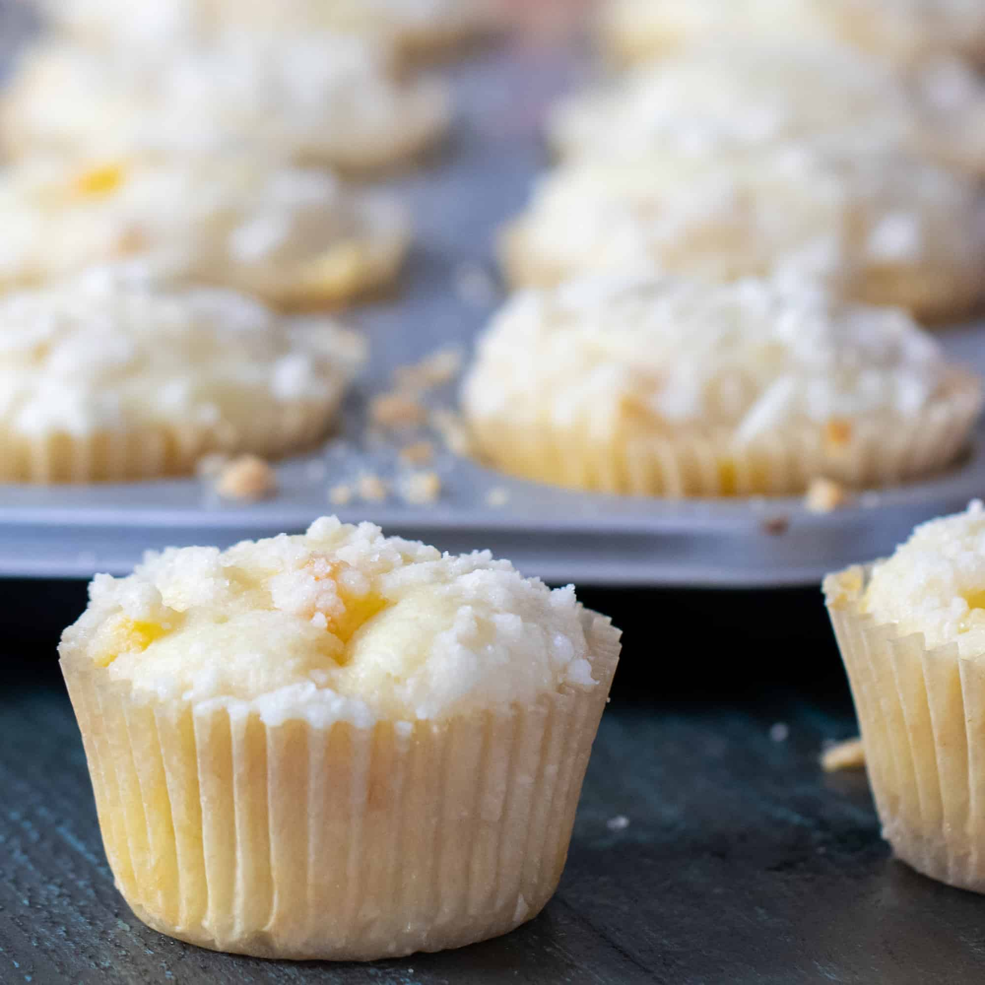Fresh baked peach cobbler muffins and a buttery crumble topping.