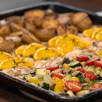 Easy recipe to make a one pan meal with frozen salmon fillets, mini potatoes and mixed vegetables. Delicious weeknight sheet pan dinner!