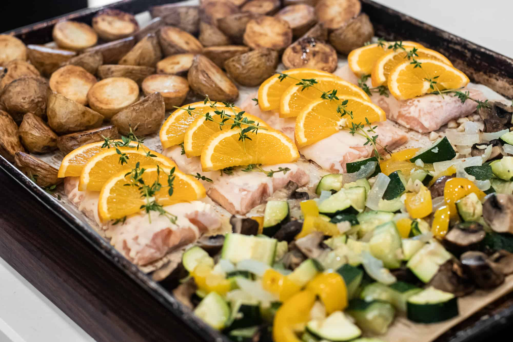 frozen salmon filet with fresh thyme sprigs and sliced oranges