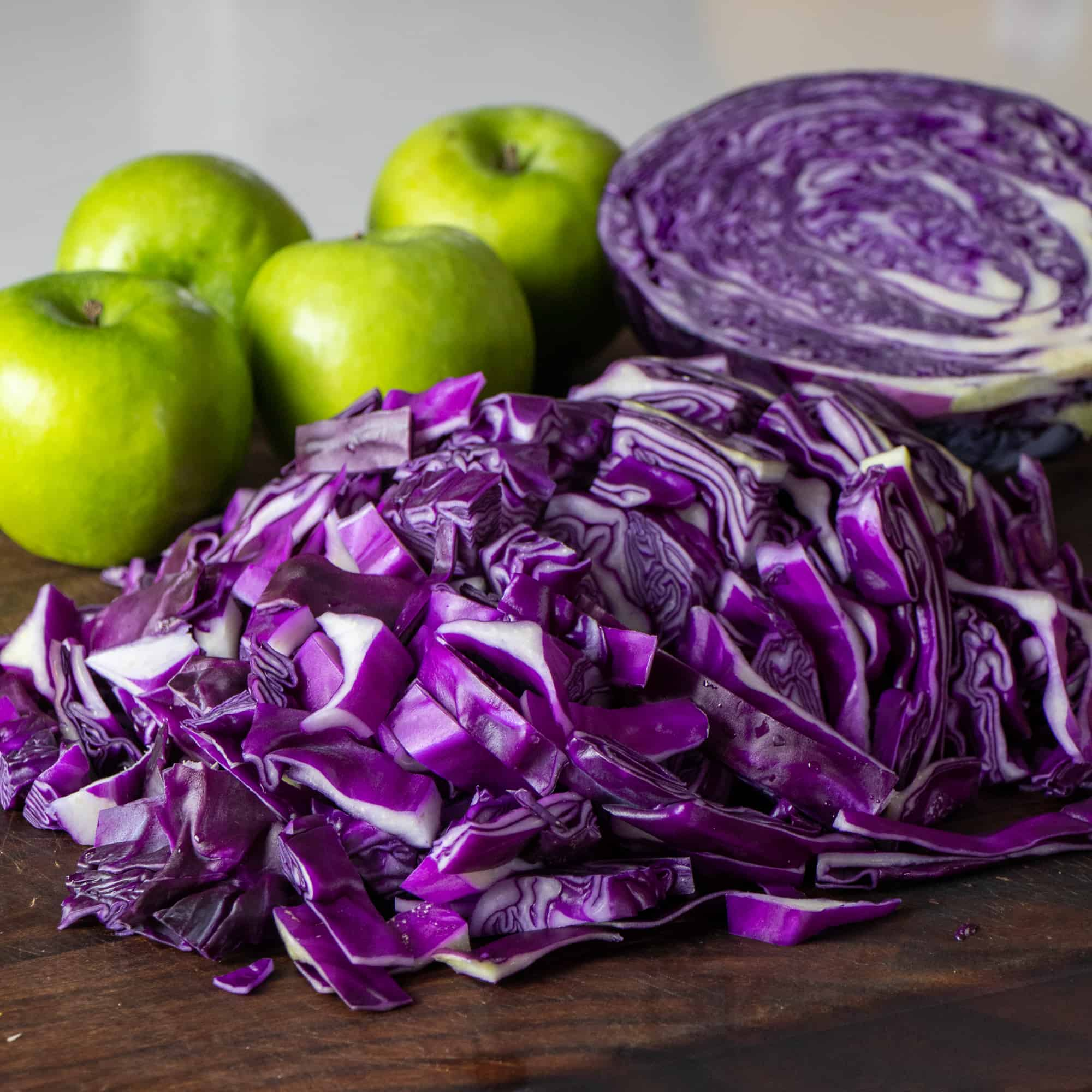 A cutting board with chopped up fresh red cabbage with granny smith apple behind it.