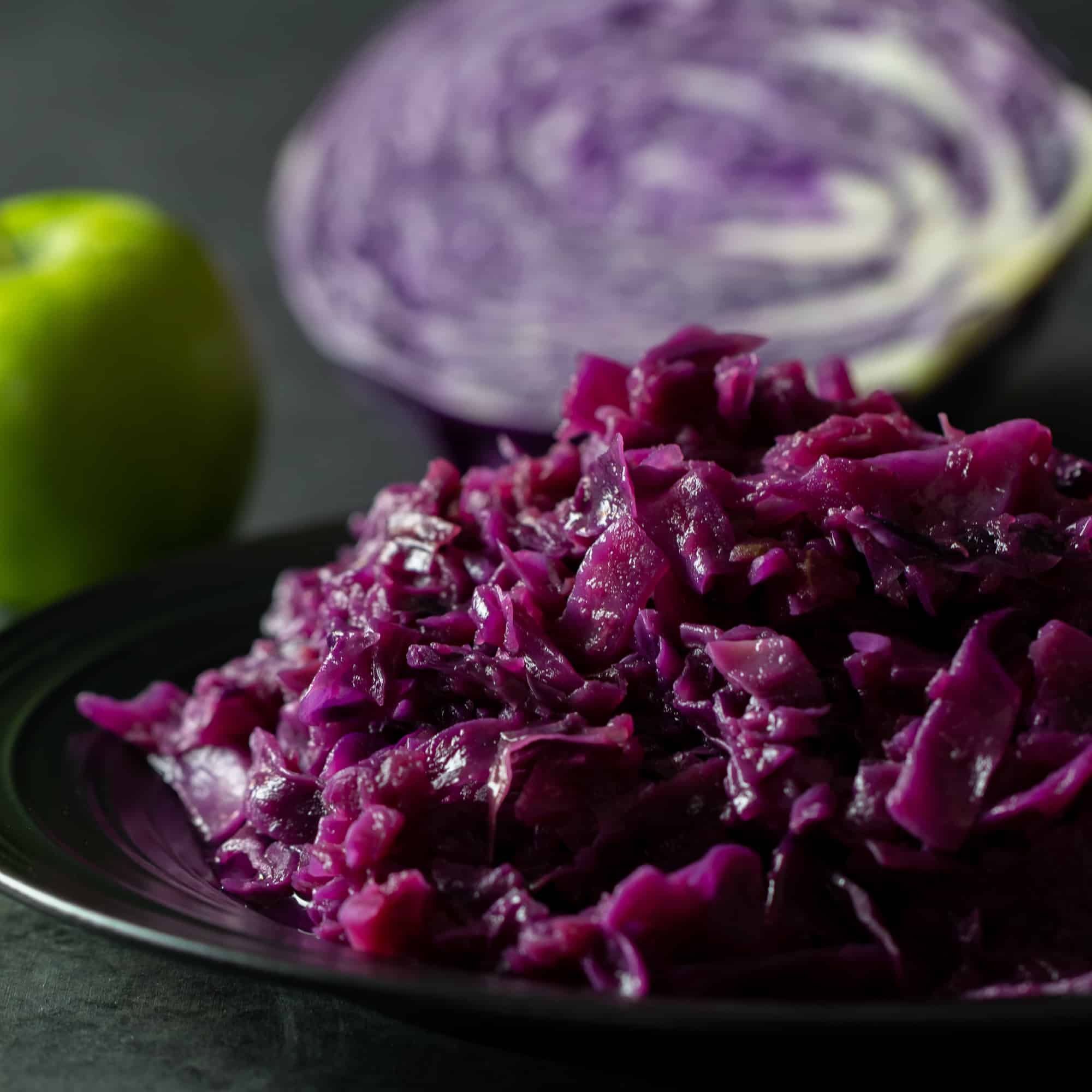 Square image of a plate of the red cabbage and apples.