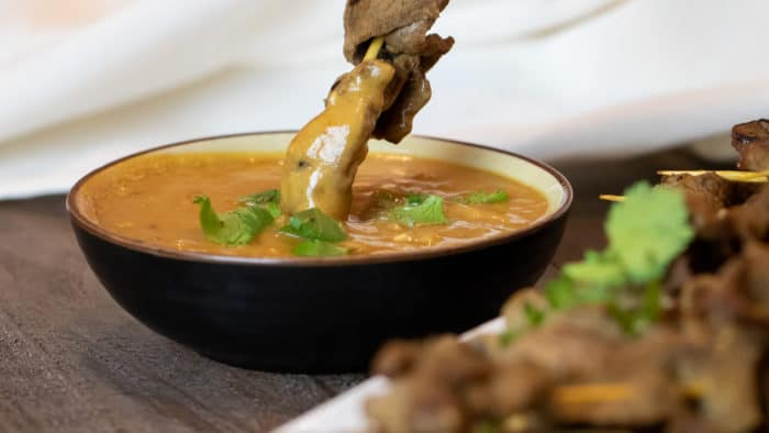 Dipping a beef satay skewer in a bowl of Thai peanut sauce