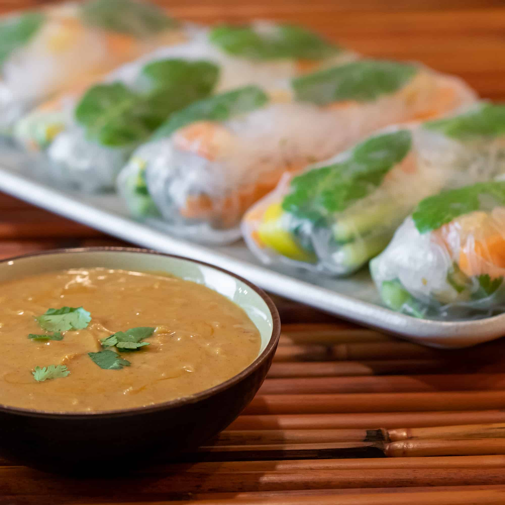 A bowl of peanut sauce with a plate of Thai cold spring rolls