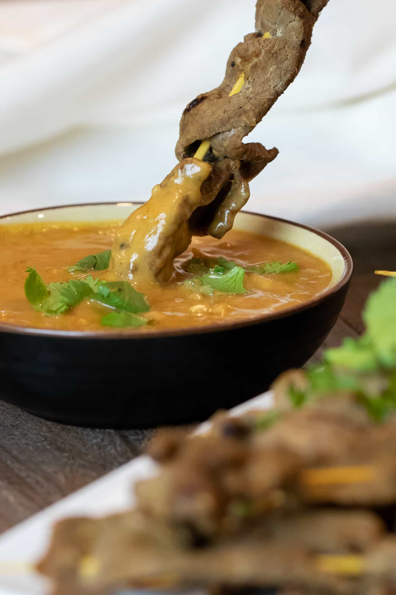Beef satay dipped in a bowl of Thai peanut sauce