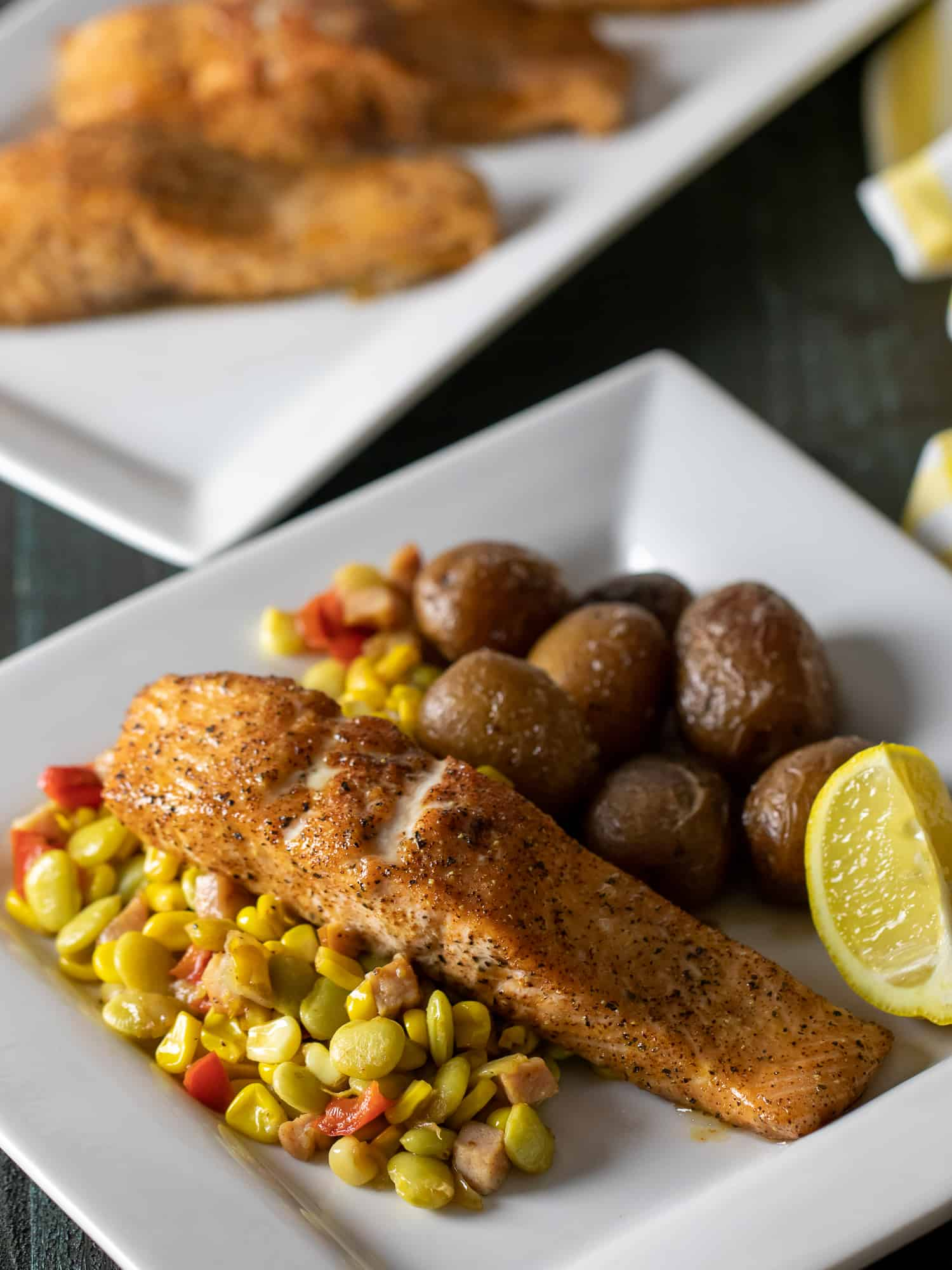 Overhead picture of plate of baked salmon fillets with potatoes, corn and lima beans.