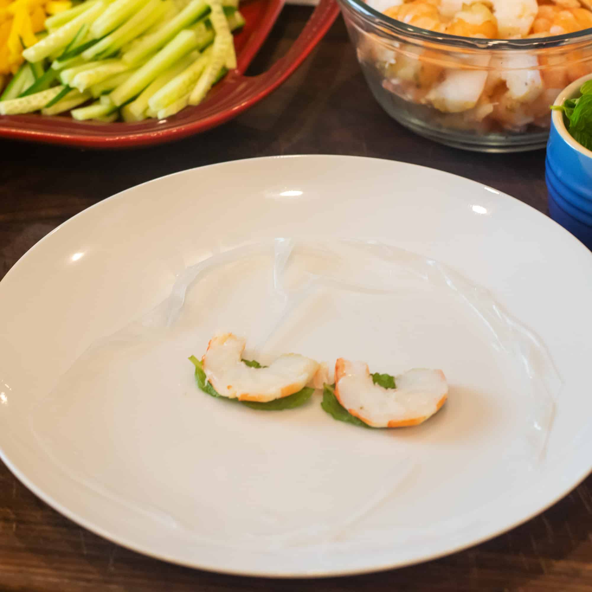 Place softened rice paper on a plate and place some fresh mint and shrimp in the centre.
