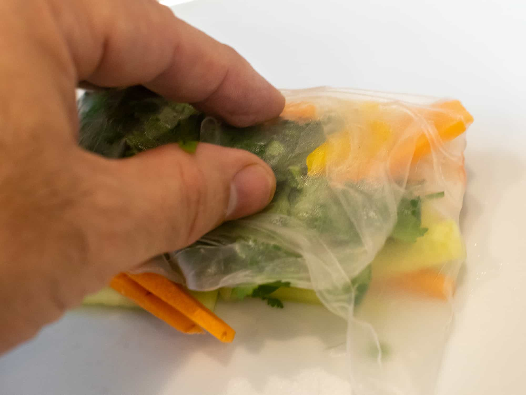 Pull the sides of the rice paper into the centre and press down to stick.