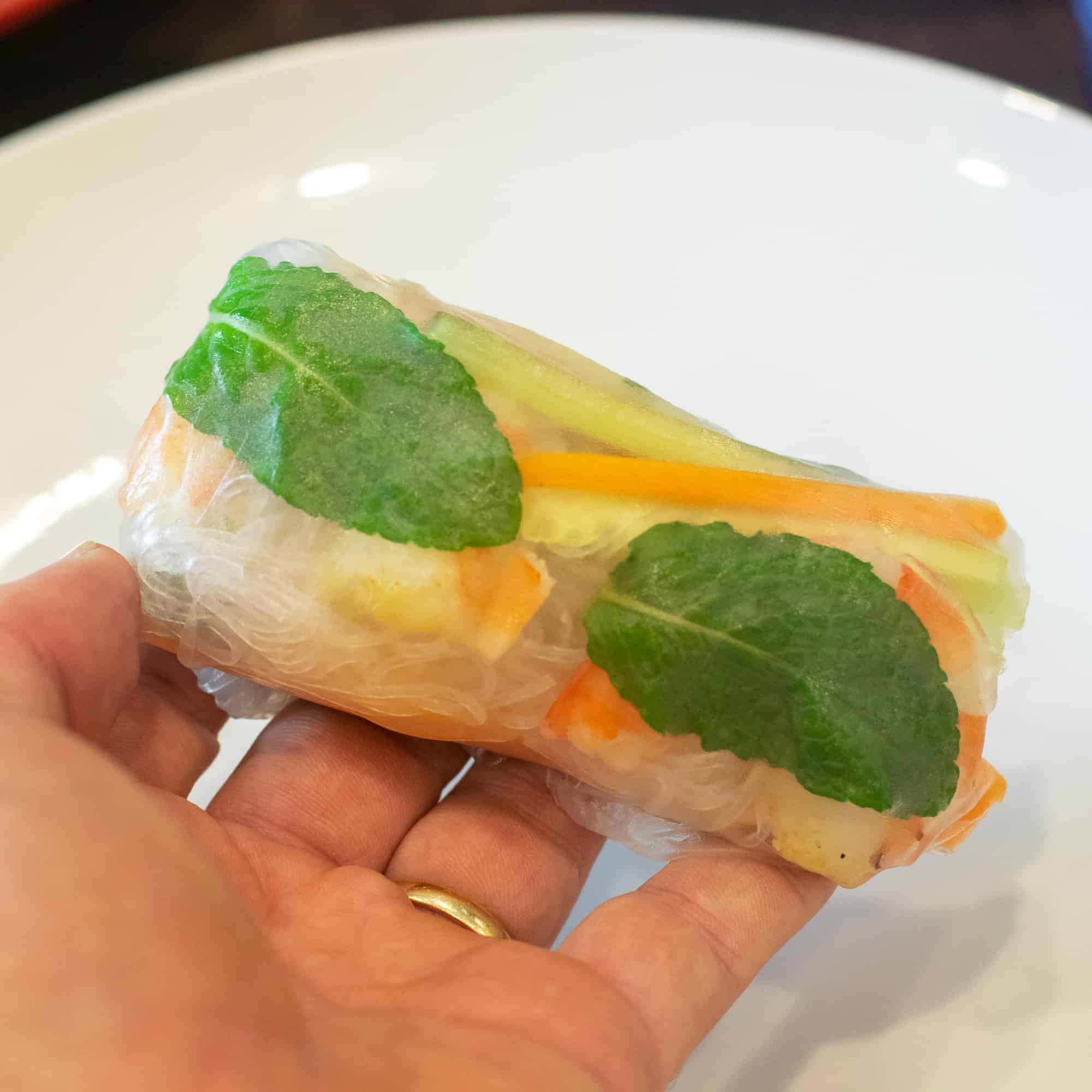Finish wrapping the Vietnamese spring by pulling the final side of the rice paper over the middle and roll it up.