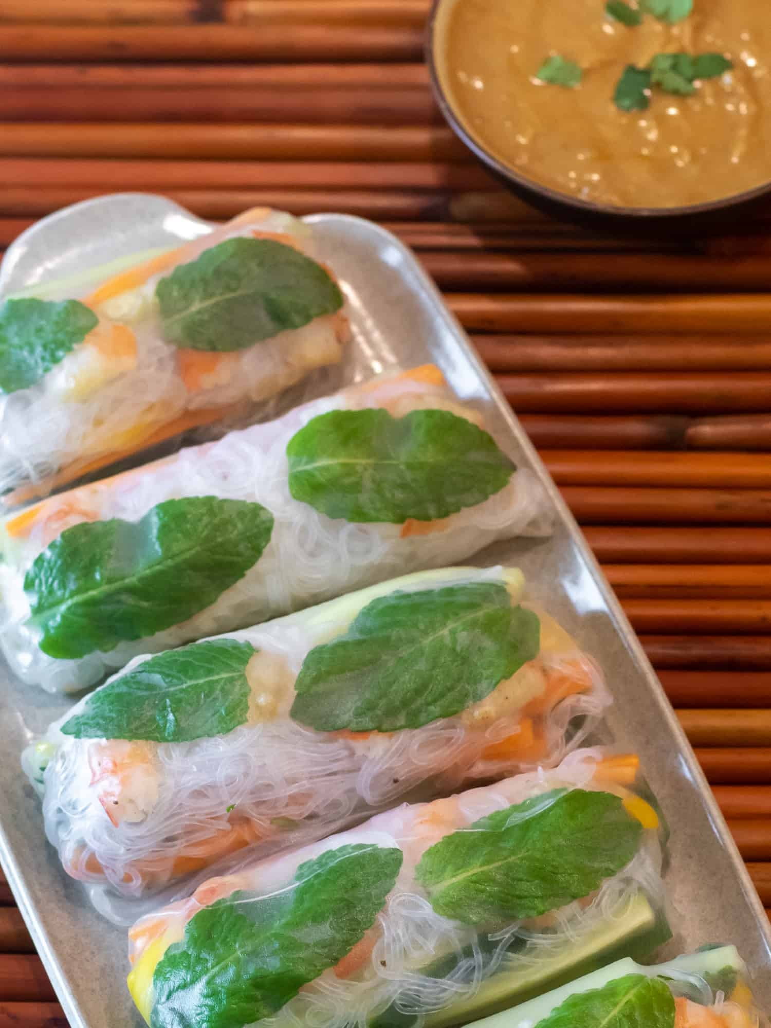 Overhead picture of plate of Vietnamese cold spring rolls with bowl of peanut sauce