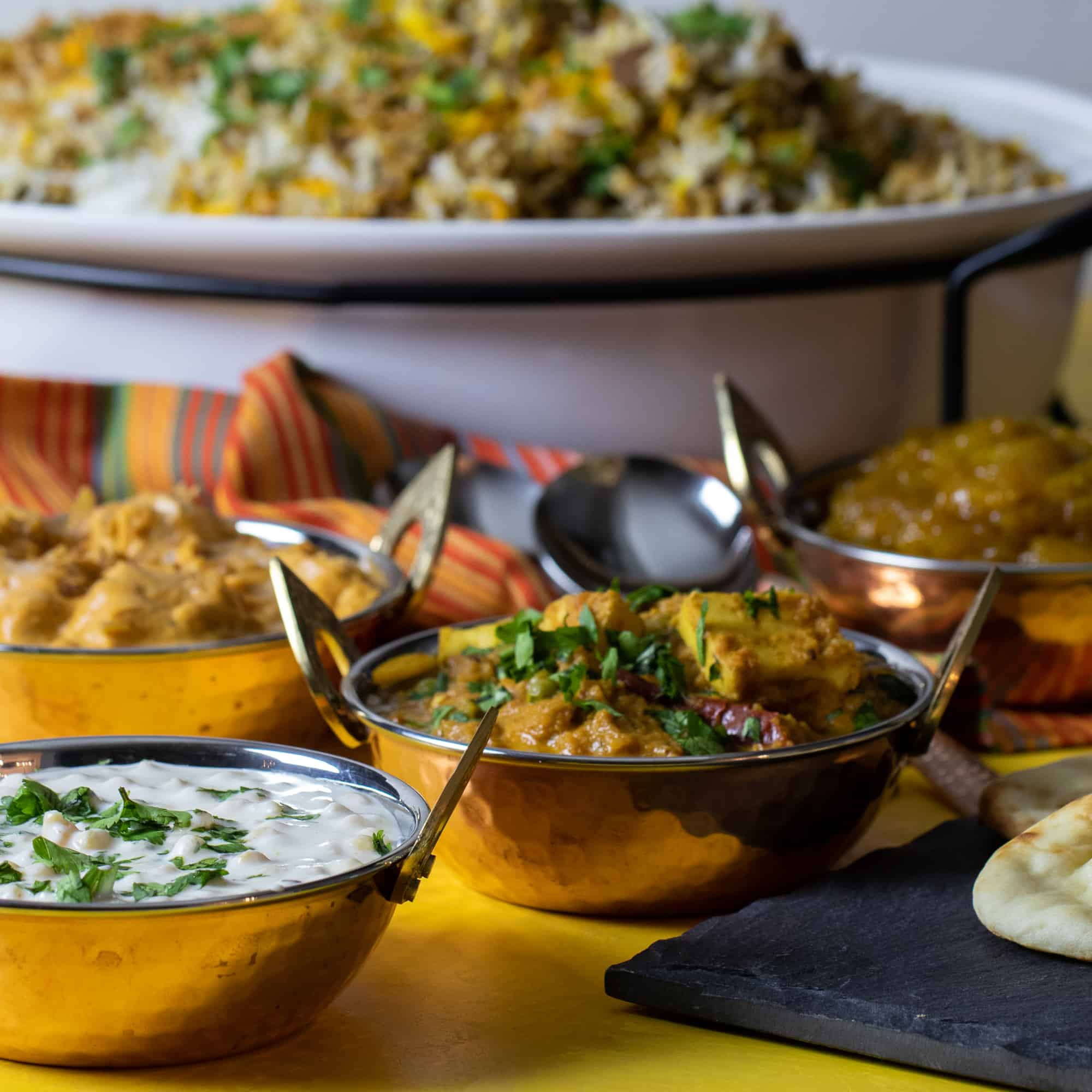 A photo of a full indian dinner including biryani, butter chicken, raita, mango chutney and matar paneer.