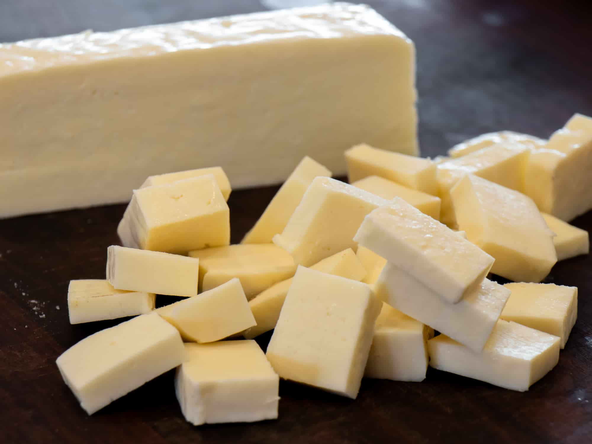A one pound brick of paneer cheese cut into chunks for Indian matar paneer.
