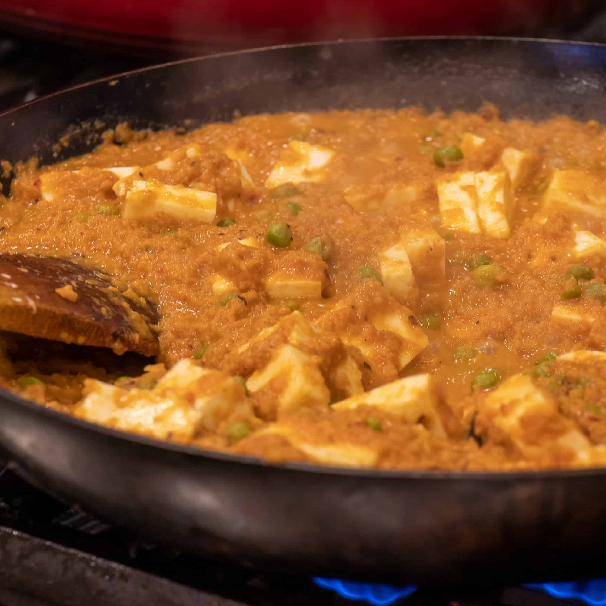 Stir in some more water, curd and cubed paneer cheese.