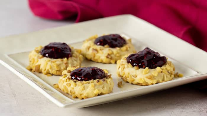 Classic recipe for thumbprint cookies rolled in chopped walnuts with a dollop of raspberry jam on top. Easy recipe and perfect for Christmas holiday baking.