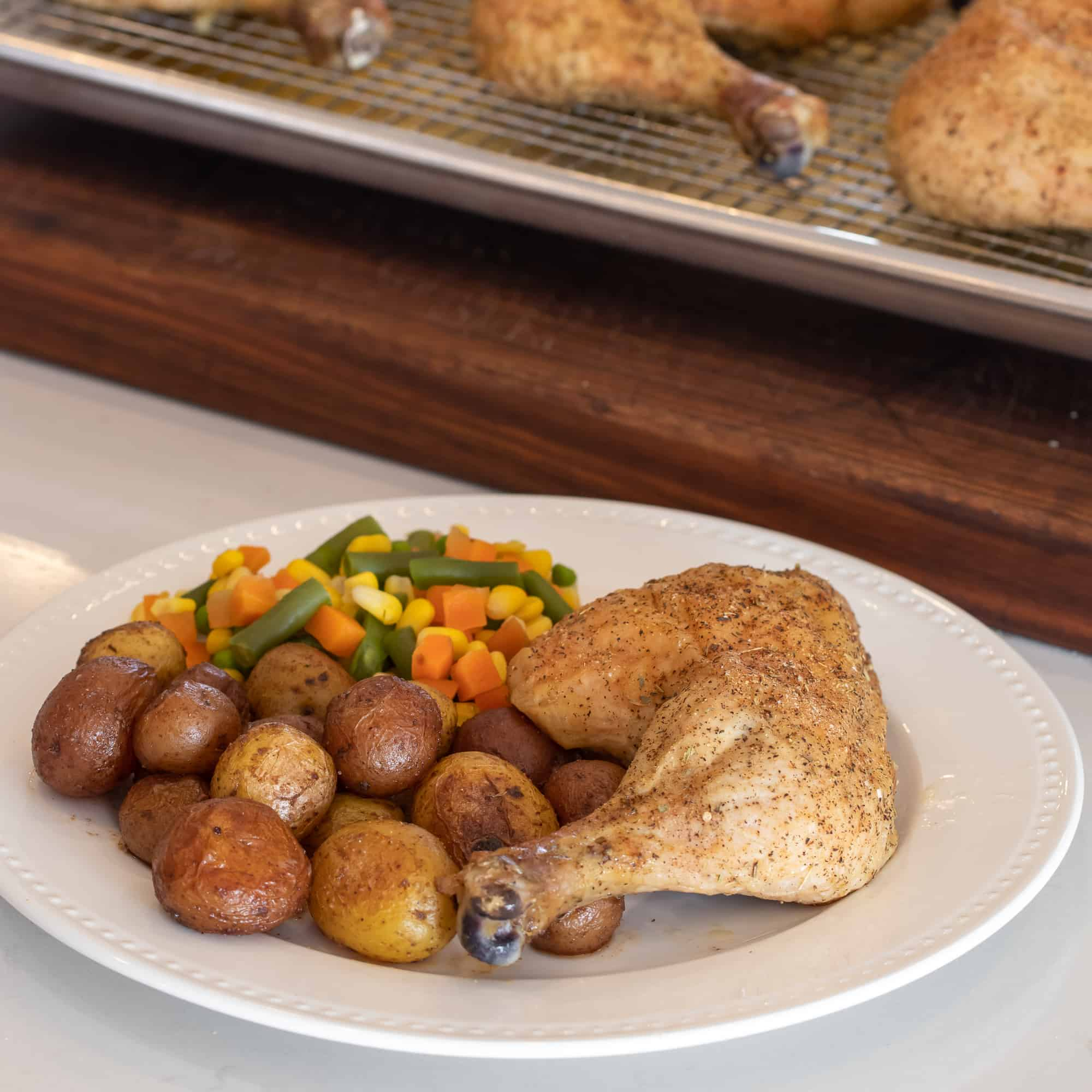 Baked chicken leg on a plate with mini potatoes and mixed vegetables.