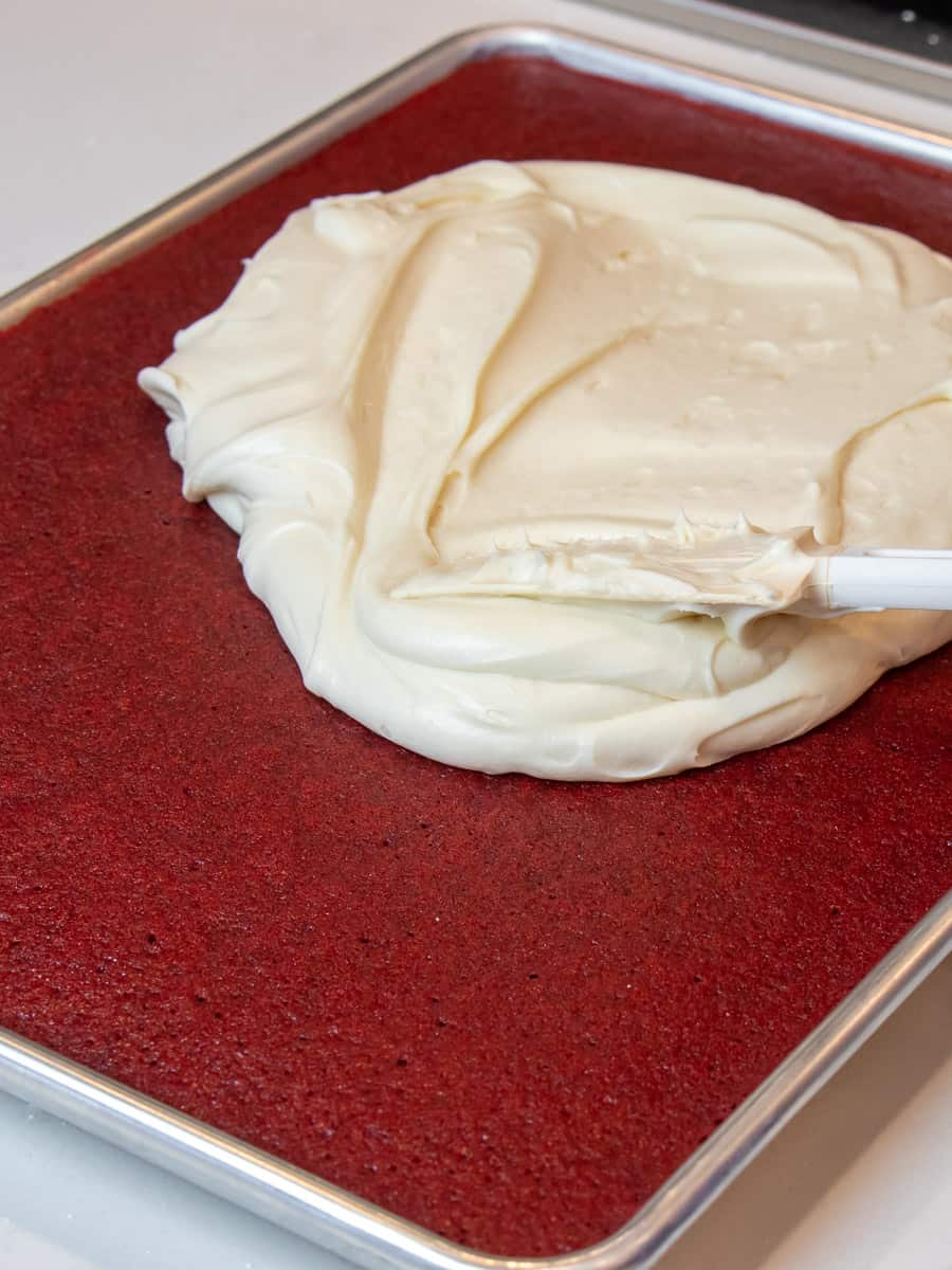 Spreading cream cheese frosting on cooled cake.