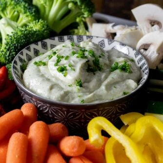 Creamy vegetable dip with raw carrots, peppers, cucumber, broccoli, and mushrooms.