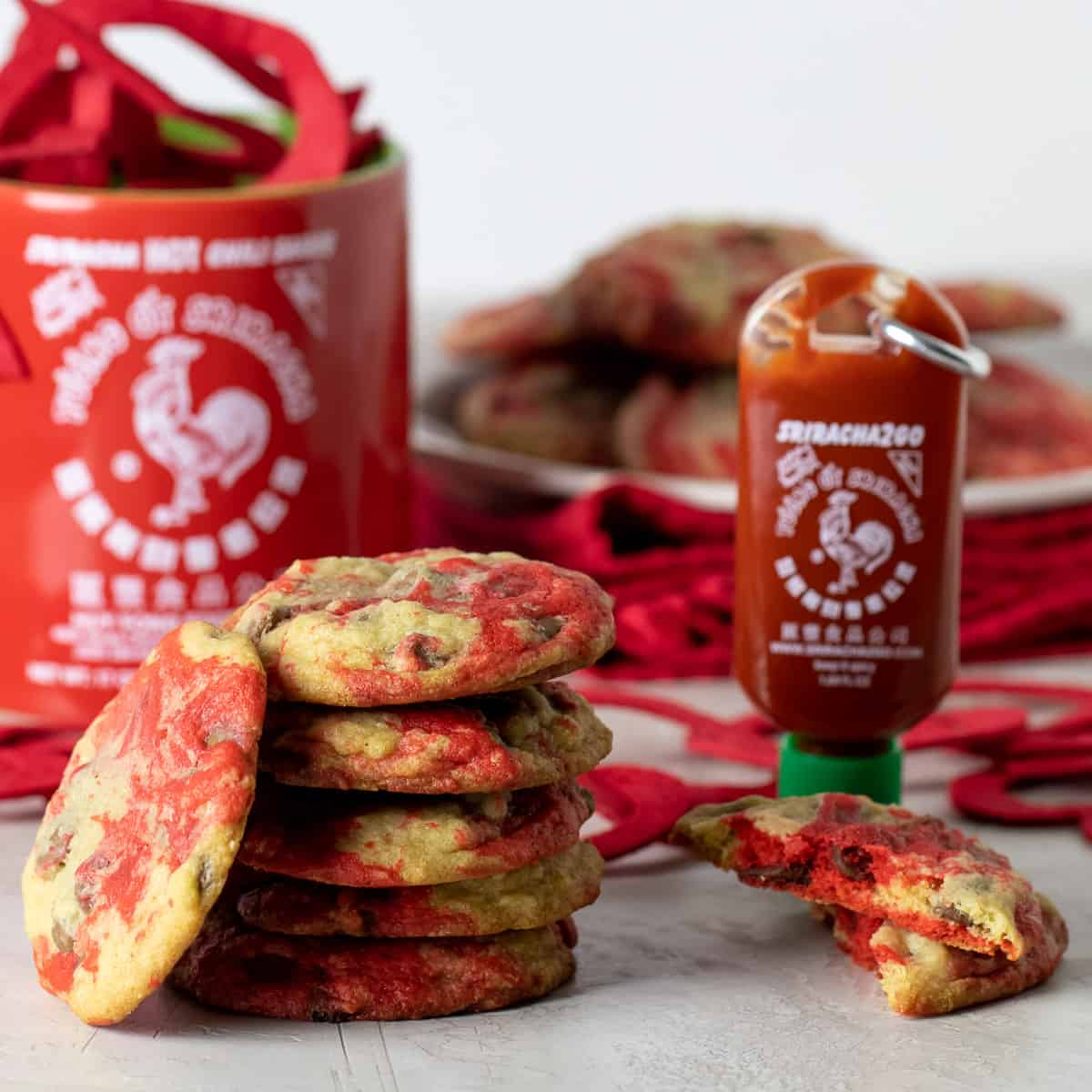 A stack of cookies next to a mug and bottle of Sriracha sauce