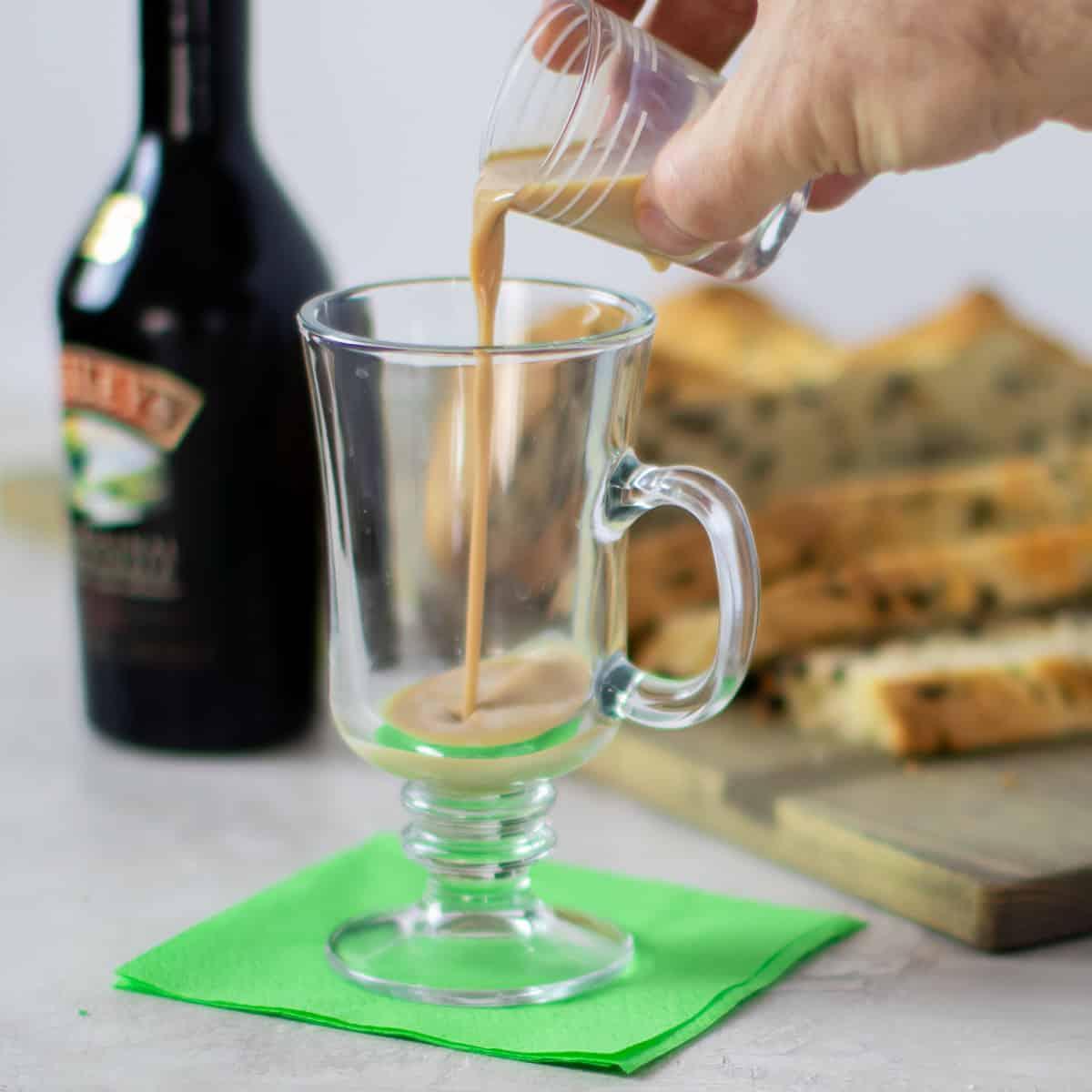 Pouring Irish cream in the glass mug.