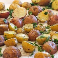 A baking sheet of mini potatoes.