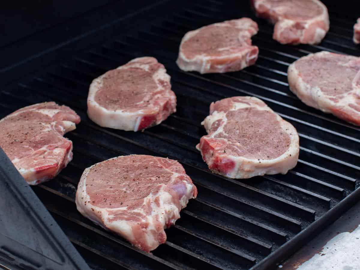 Raw seasoned chops on a grill.