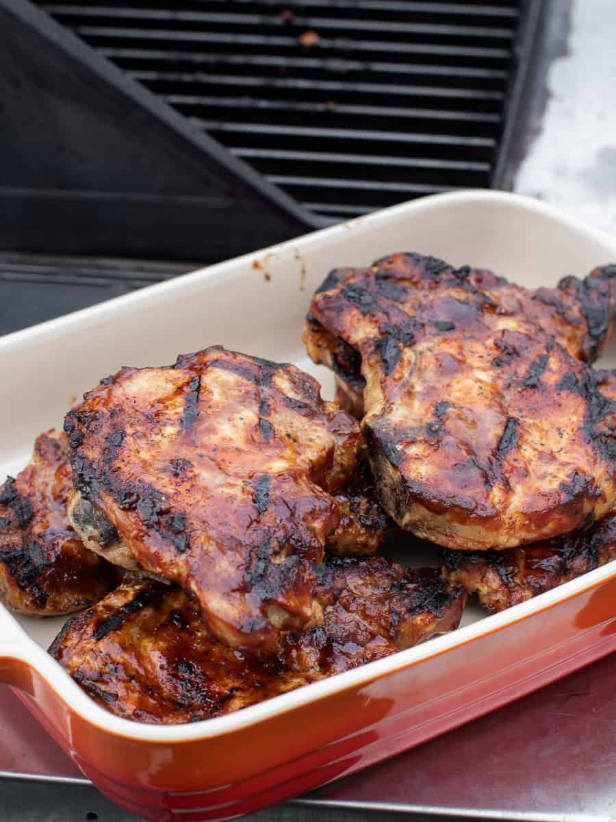 A serving dish of cooked pork chops with lots of BBQ sauce.