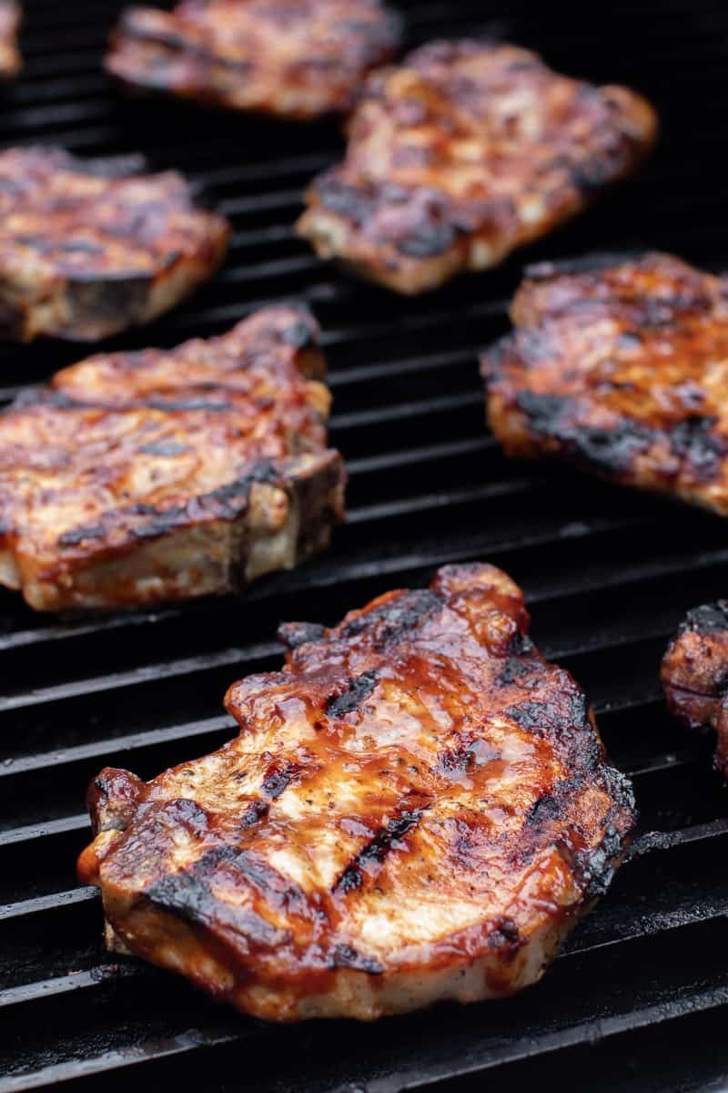 Tall image of meat on a grill.