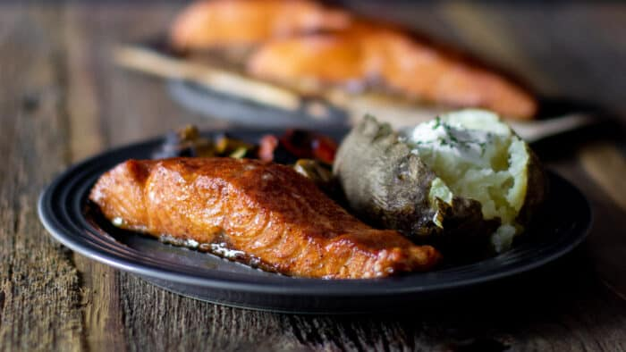 A plate of grilled salmon and a baked potato.