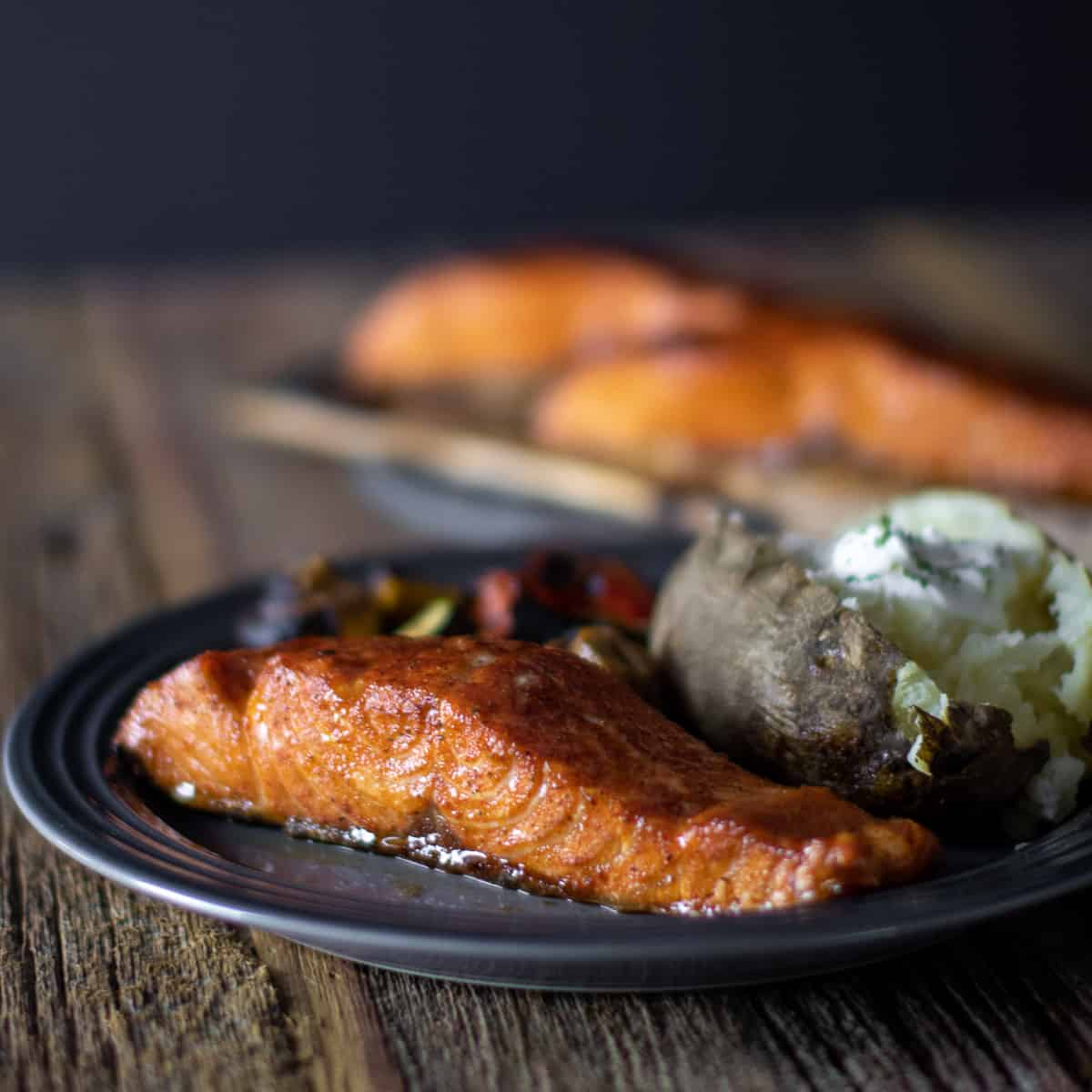 A close up picture of a dinner plate with salmon and baked potato.