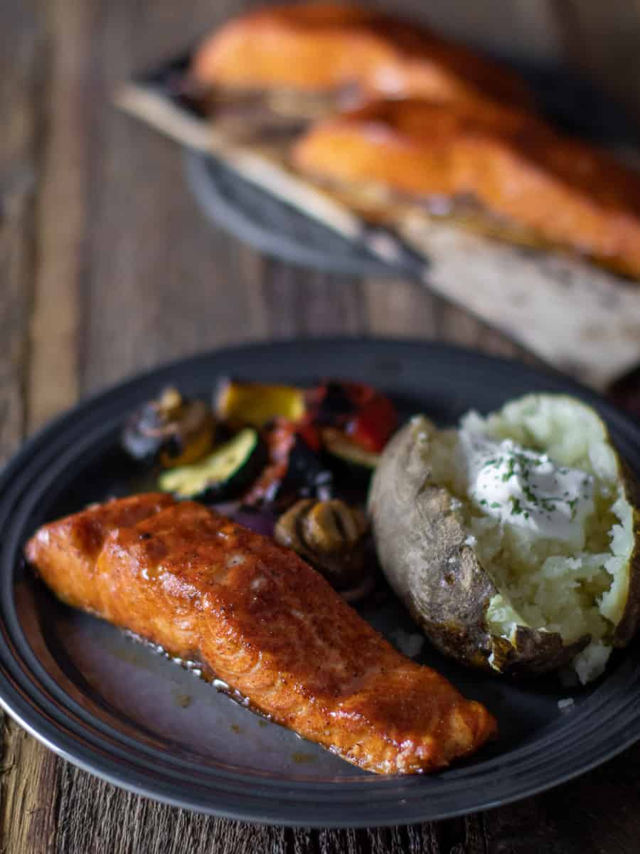 A plate of food with a plank with two fillets of salmon in the background.