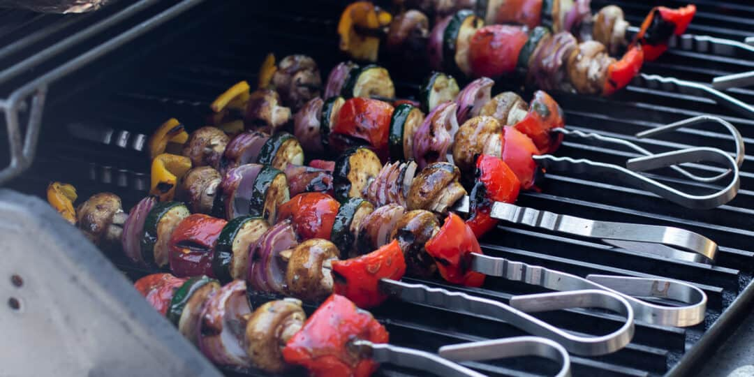 Skewers of vegetables on a grill.