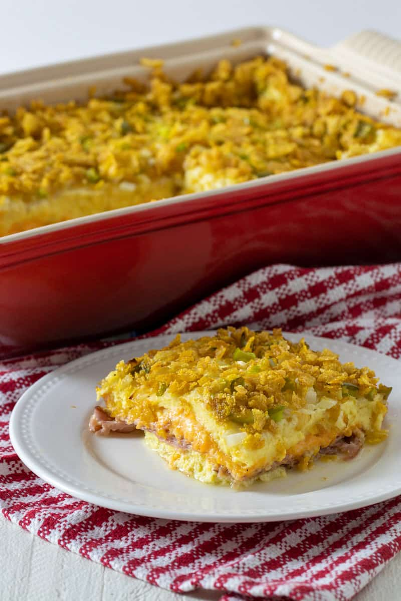 A slice of casserole on a plate in front of baking dish.