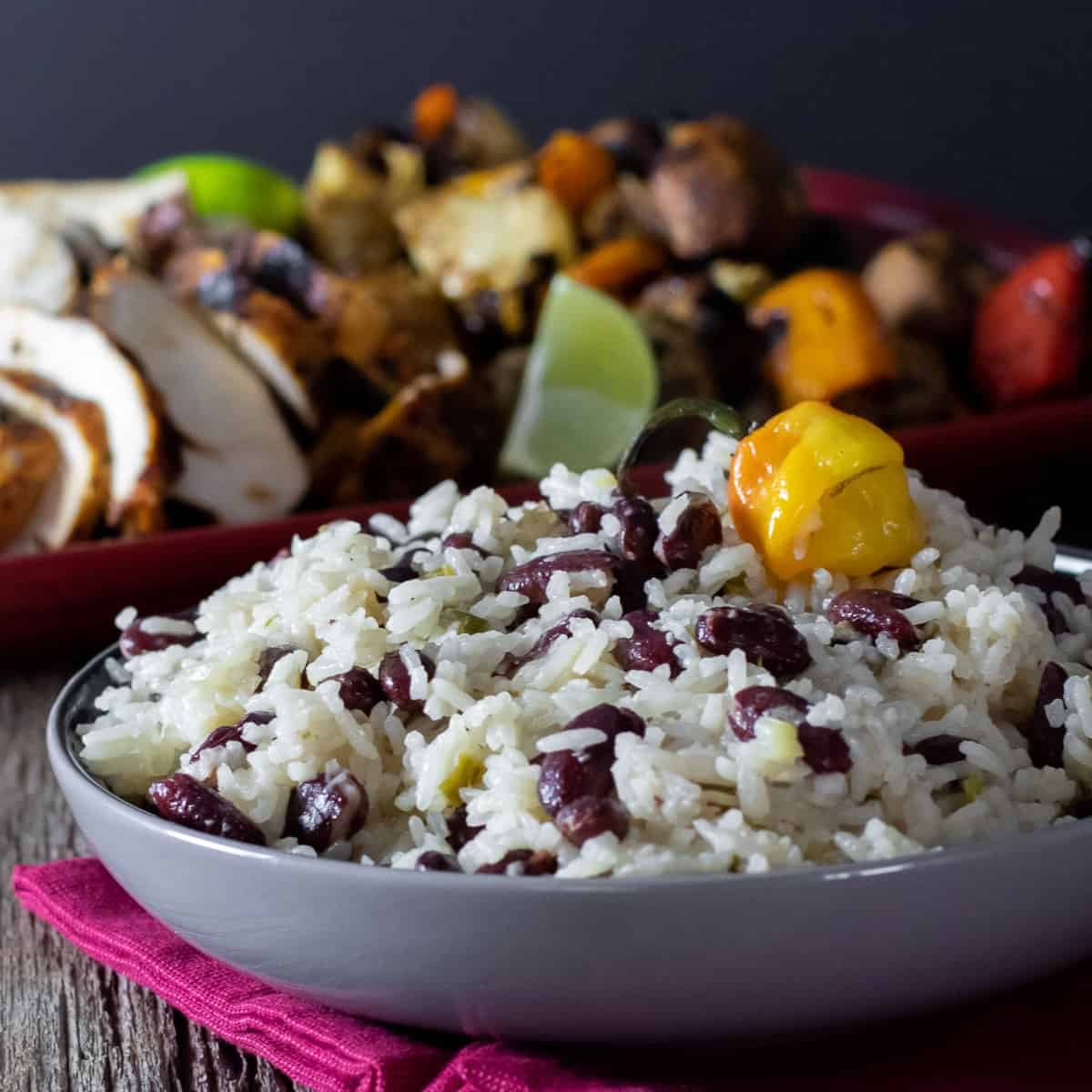 A bowl of rice and beans with a platter of chicken and vegetables in the background.