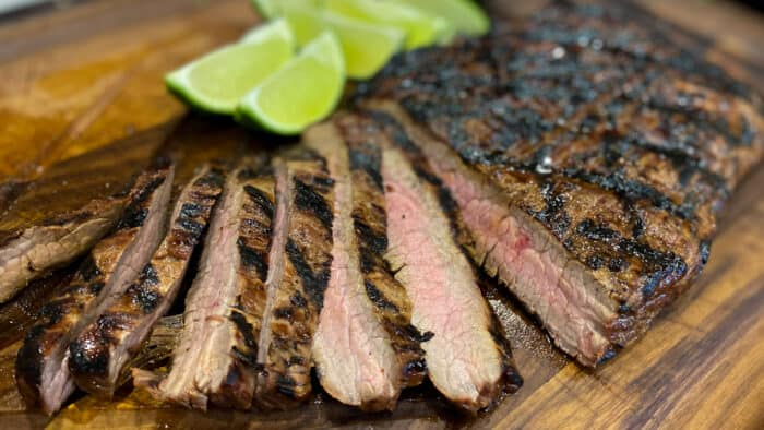 Flank Steak on a cutting board with lime wedges.