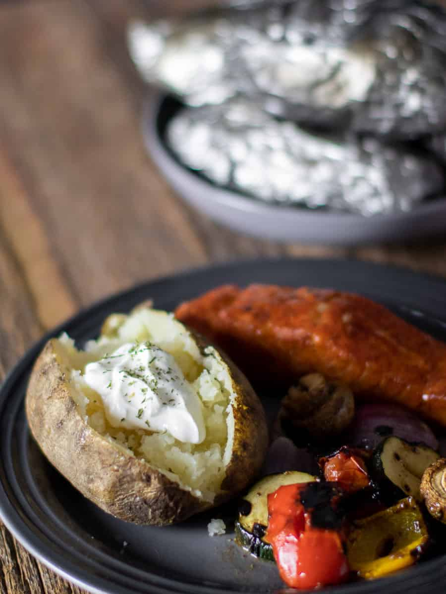 A plate with a baked potato, grilled salmon and vegetables.