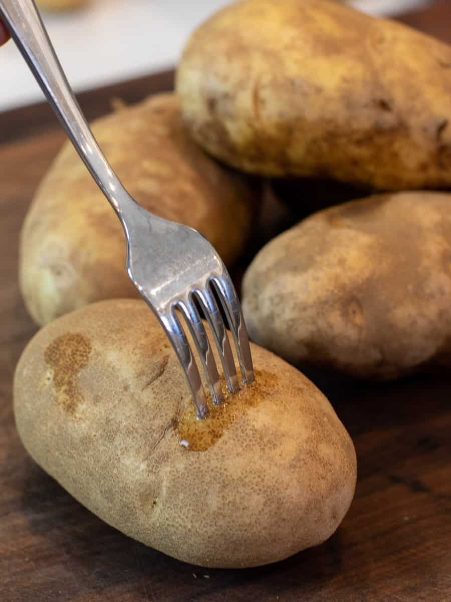 A fork pierced into a russet potato.