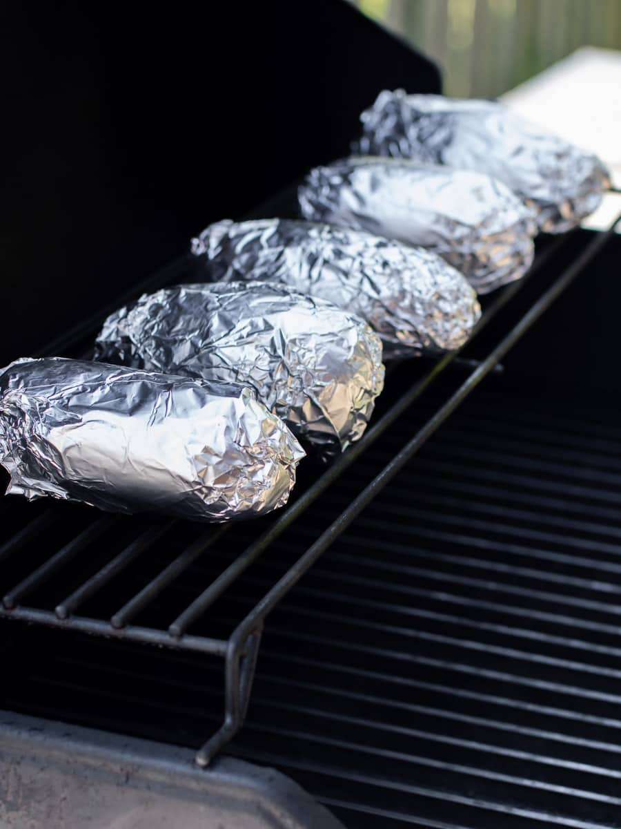 Wrapped potatoes on the upper rack of a grill.