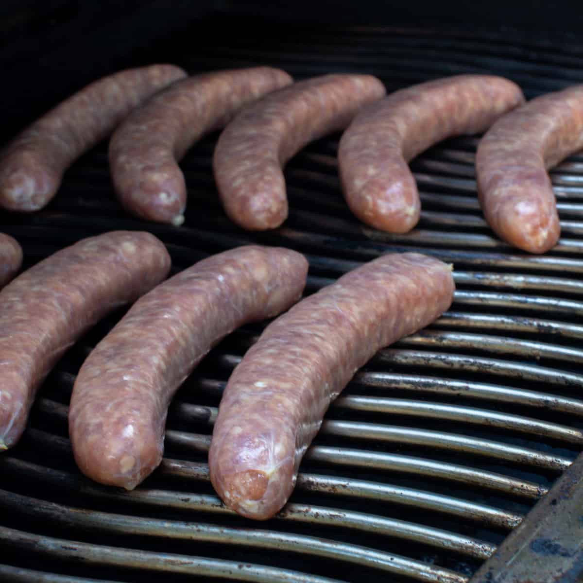 Raw sausages placed on a grill.