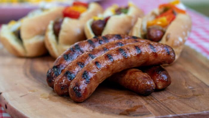 Grilled Italian Sausages with buns and toppings.