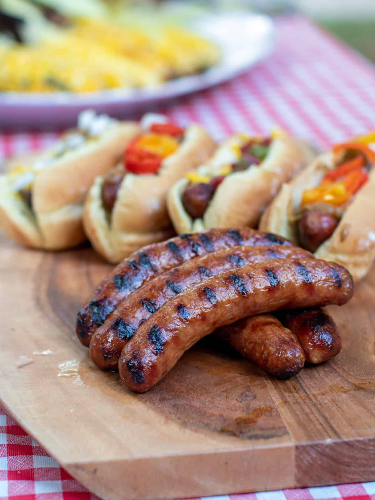 A picnic with sausages on a bun and corn on the cob.