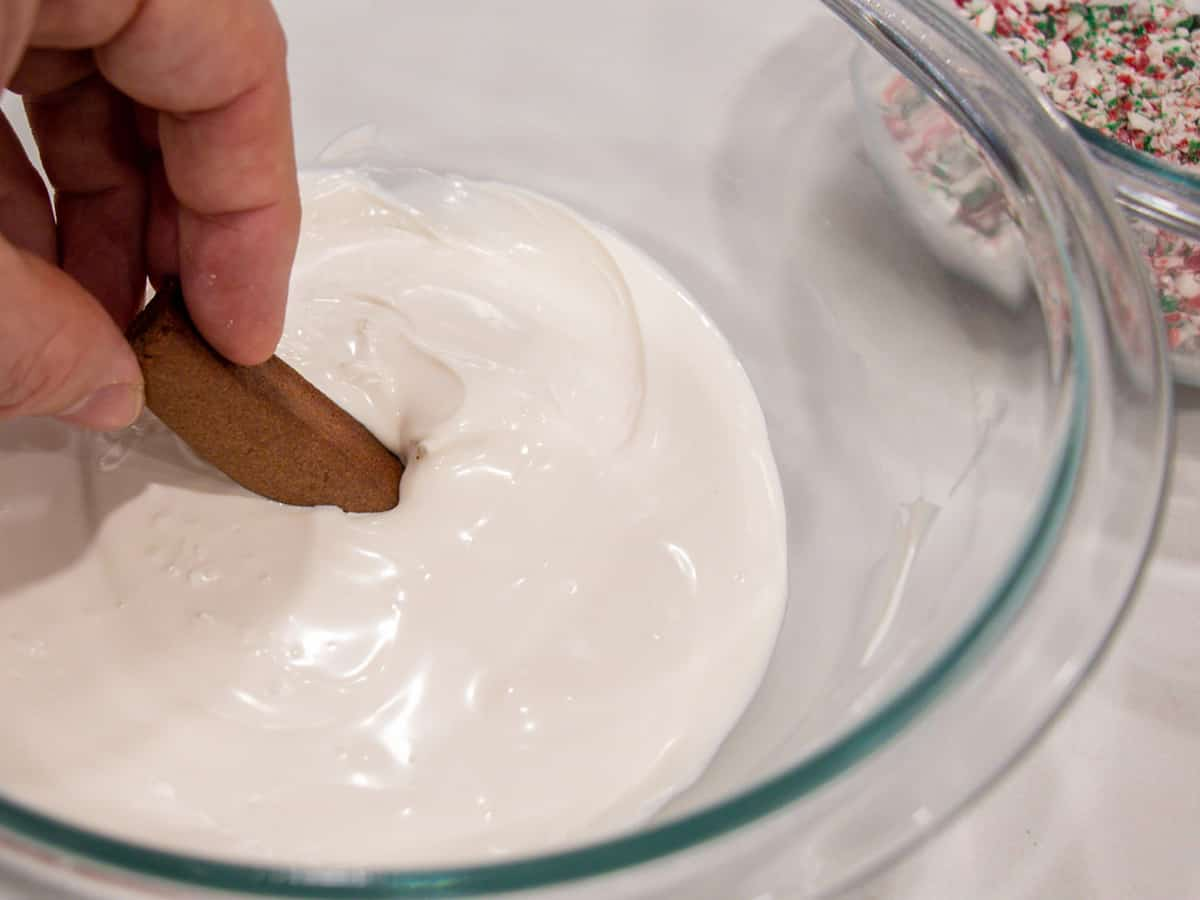 Dipping a chocolate cookie in melted white chocolate.