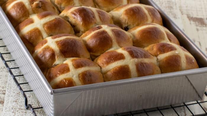 A rectangular baking dish full of fresh baked buns.