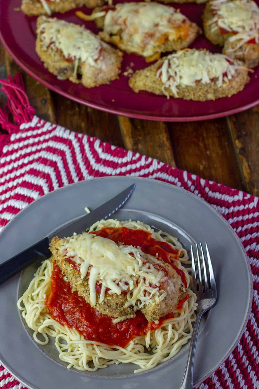 An over head picture of a plate of chicken parmesan next to a plate with more chicken.