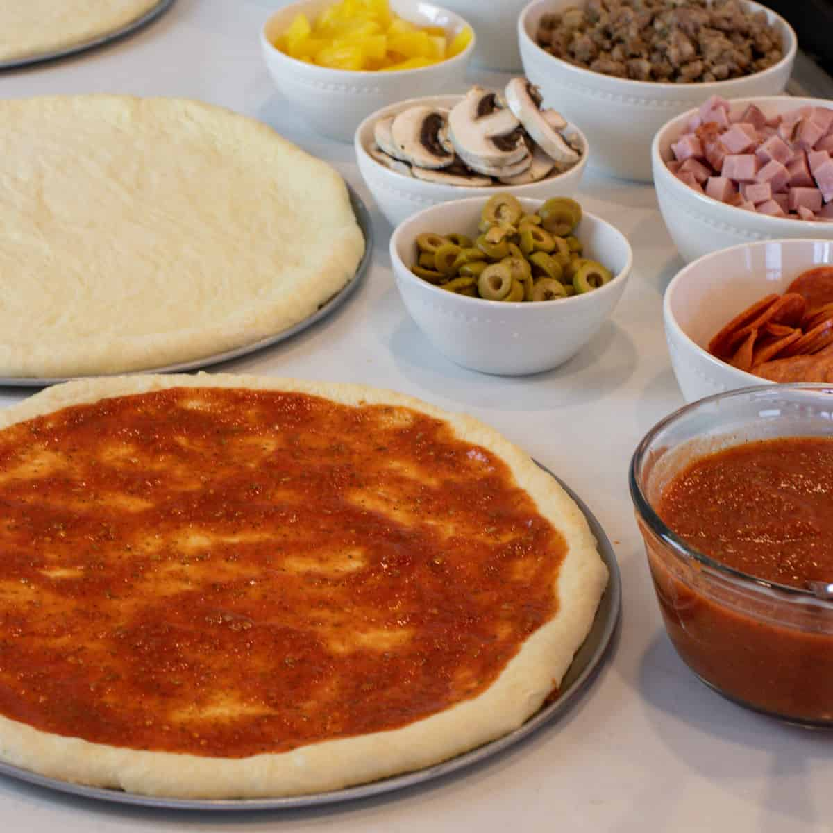 Pizza crust with fresh sauce spread all over.