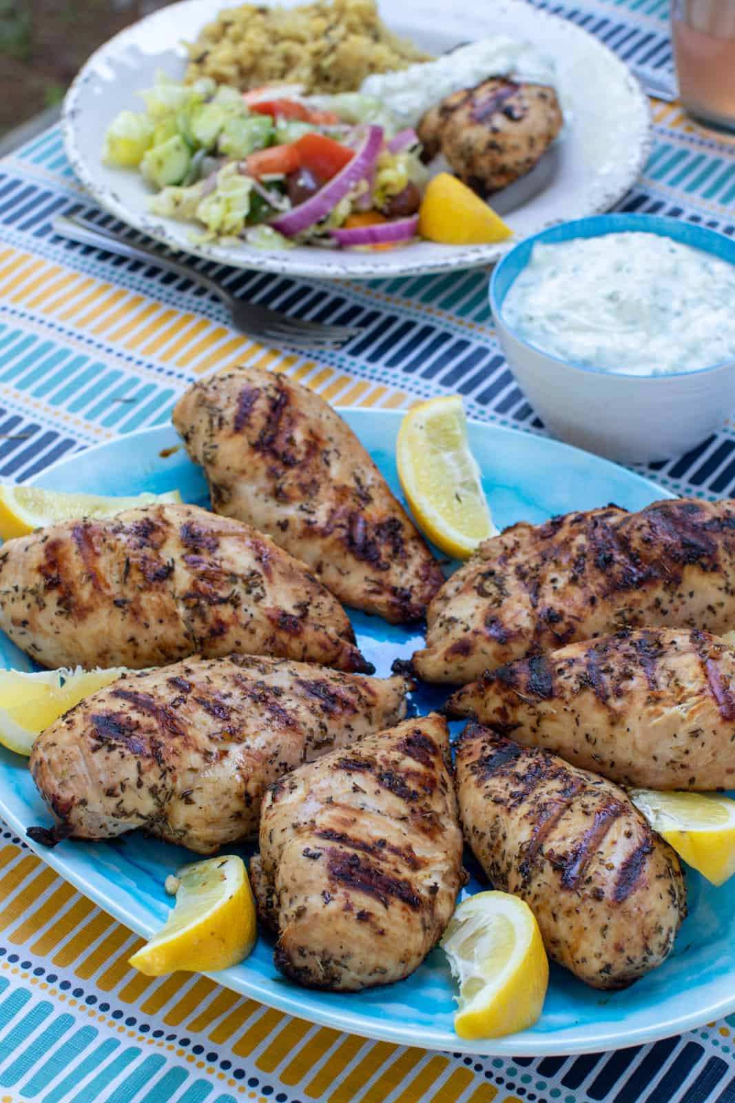 A platter of Grilled Greek Chicken with lemon slices.