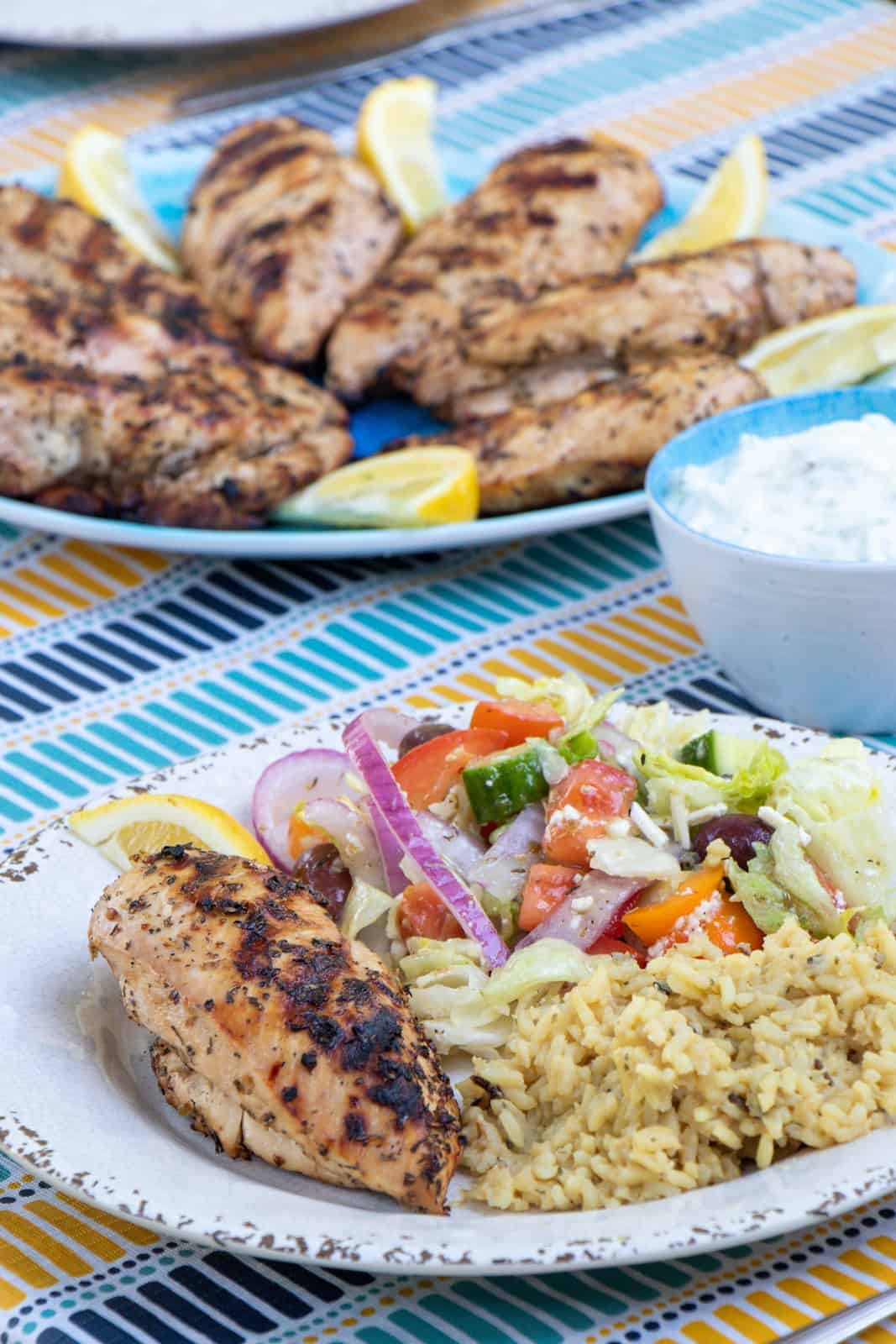 A plate with chicken, rice and Greek salad.