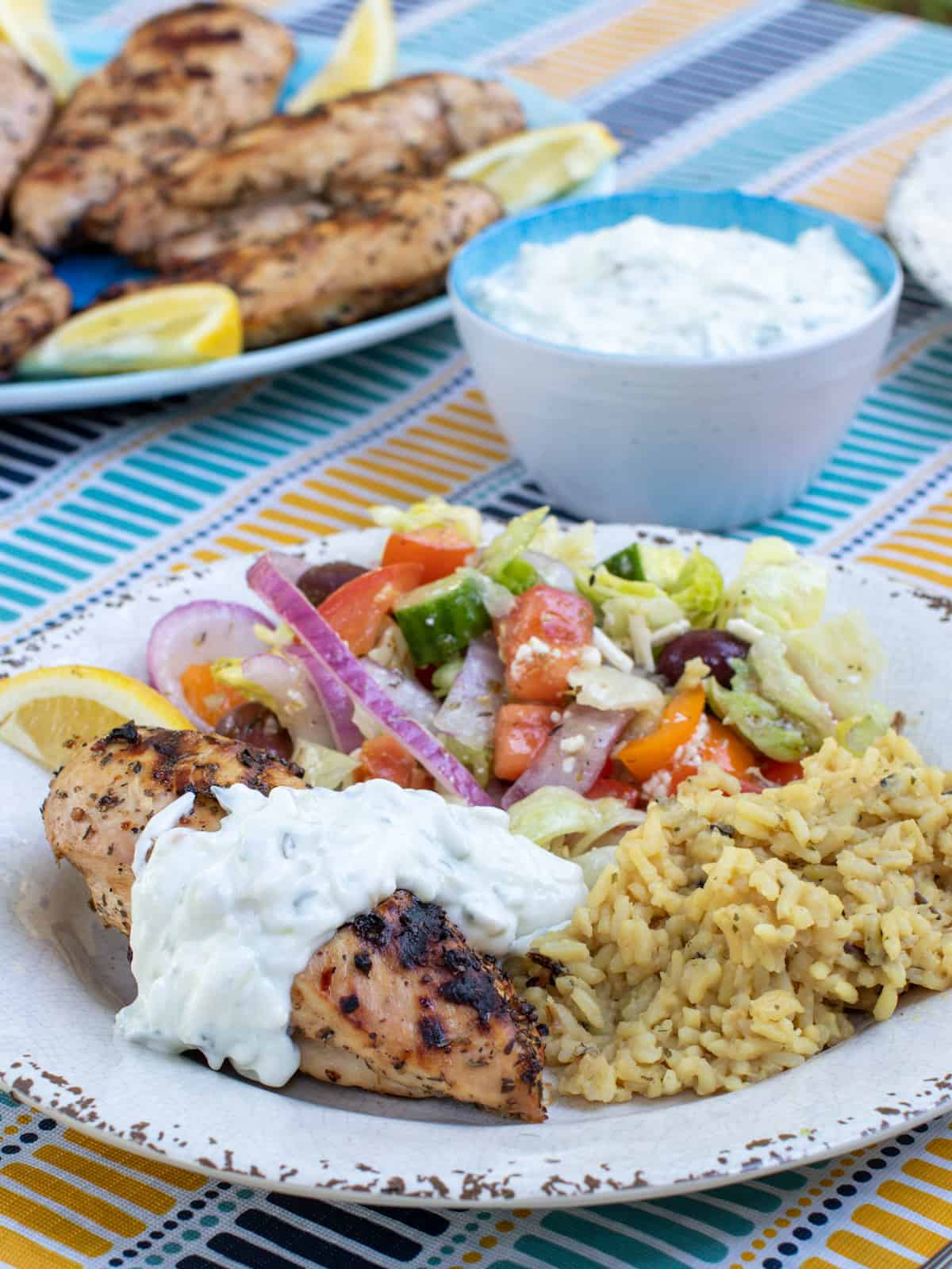 A plate of Greek food including chicken, salad, rice and tzatziki